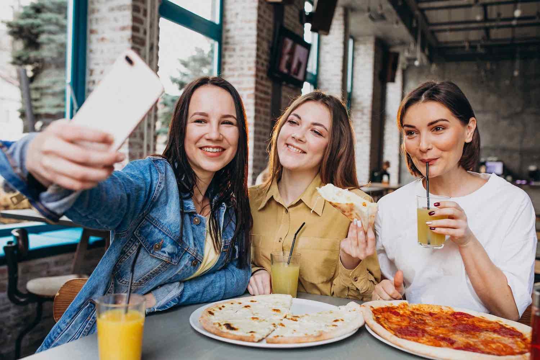 amigas tomando pizza imagen para describir