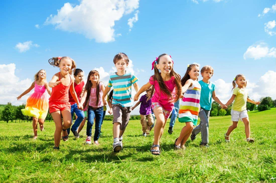 A large group of kids running in the park