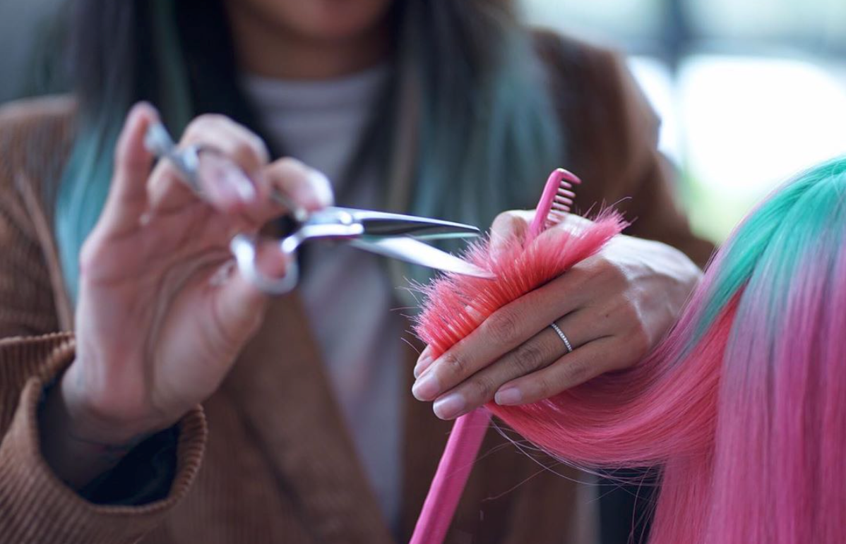 A picture depicting a hairdresser doing styling and final touches on pink hair