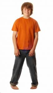 A young boy in an orange top is standing intoed or pigeon toed.