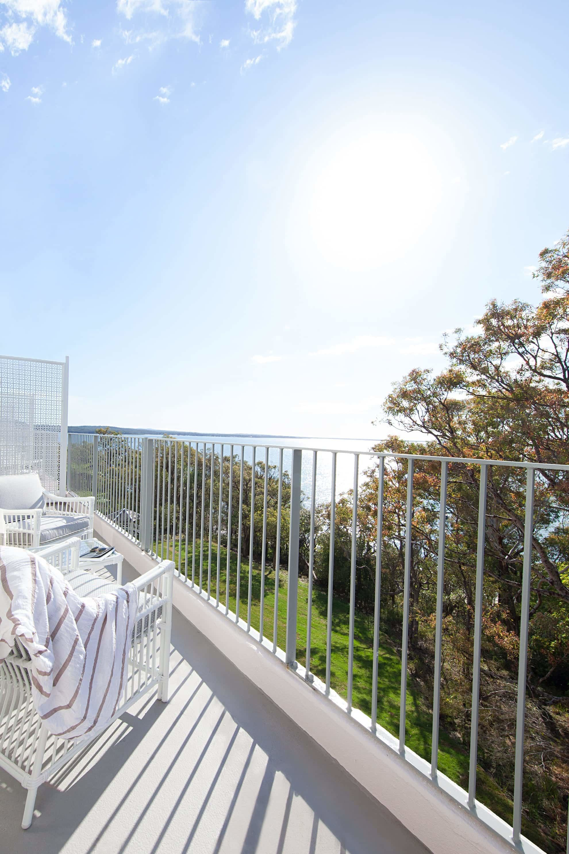 balcony view onto grass and bright blue skies
