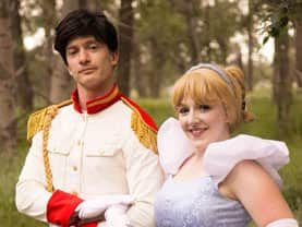 Prince Charming lending an arm to the Cinder Princess to walk in her royal princess shoes at parties in Calgary
