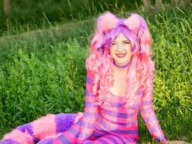 The Cheshire Cat lounging in the Calgary grass with the forest behind her, looking out for the Red Queen of Hearts