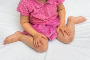 A young child sitting in W-position which is bad for the hips