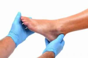 A podiatrist with blue gloves is holding a patient's foot for assessment