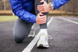 A man in running gear holds his shin