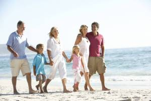 A family of three generations are walking together on a beach