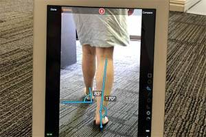 An iPad showing an analysis of a lady walking, with biometric lines drawn.