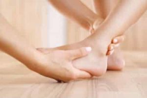 A podiatrist's hands are palpating an ankle and foot.