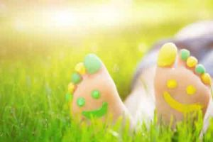 A pair of children's feet painted smiley faces on