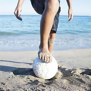 A child holds his foot on a soccer ball at the beach