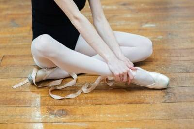A ballet dancer sits on the floor holding her Achilles Tendon