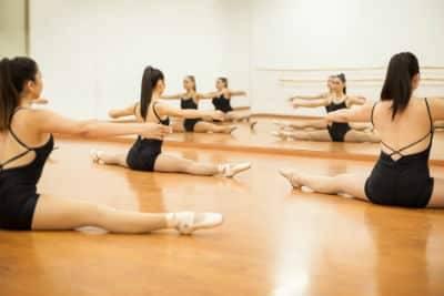 bBallet dancers doing floor stretches