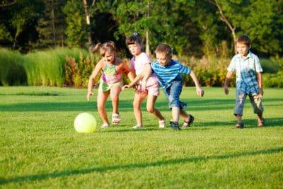 Four Children playing soccer in the park