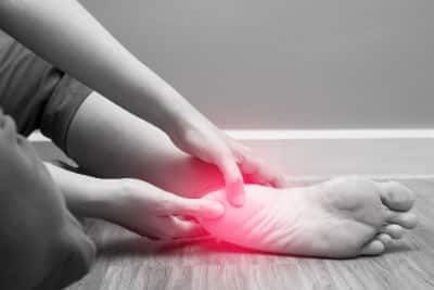 A woman holds her sore heel which is shown in red