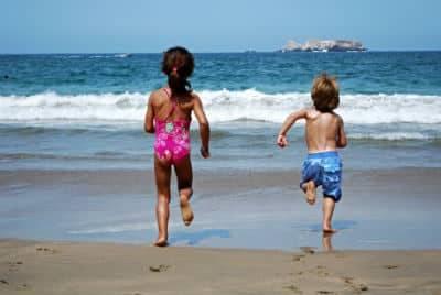 Two children running down a beach towards the ocean
