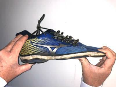 A dead shoe test - hands are trying to bend the front of a running shoe backwards.