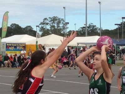 Girls playing netball. One is about to shoot