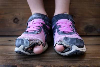 Worn out shoes with the big toes poking out of the shoes on a child