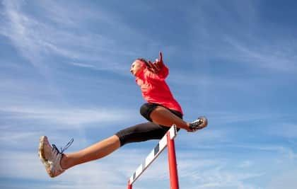 A woman hurdling with a blue sky background