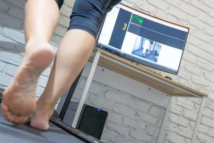 The legs and feet of someone walking on a treadmill with a screen in the background
