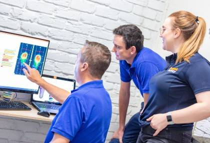 Three podiatrists analysing some information on a screen