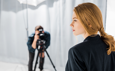 Woman being photographed by man who is feeling sleazy about sales*