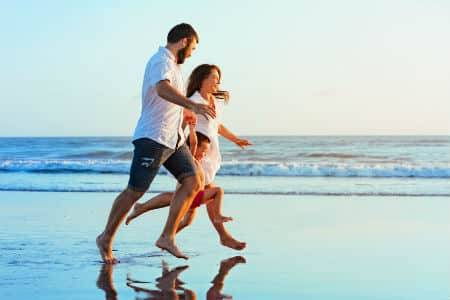 A family running barefoot on the beach