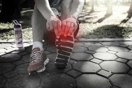 A runner holds their toe on the side of the road because it is sore
