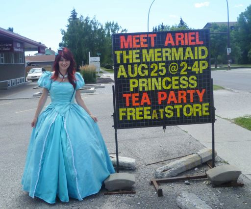 Princess Little Mermaid with Ten Thousand Villages Princess Tea Party Sign outside of Heritage South Calgary Store