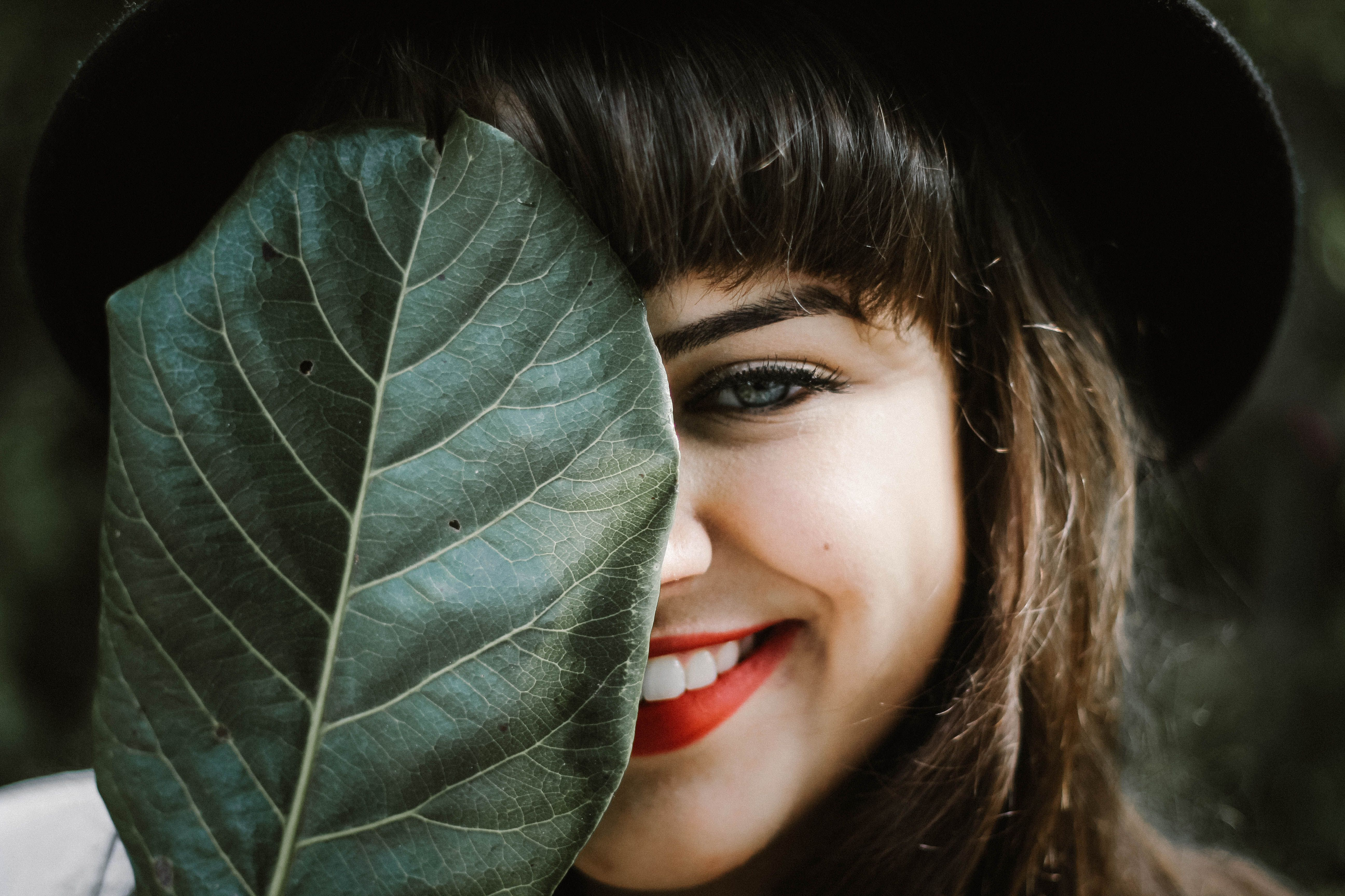 girl with bangs holding a leaf and smiling