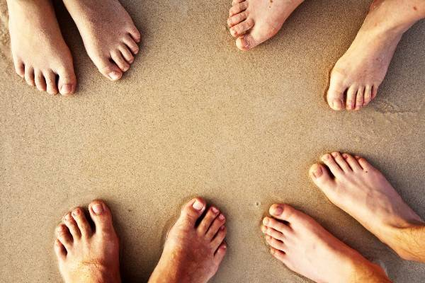 The feet of 3 people on a beach