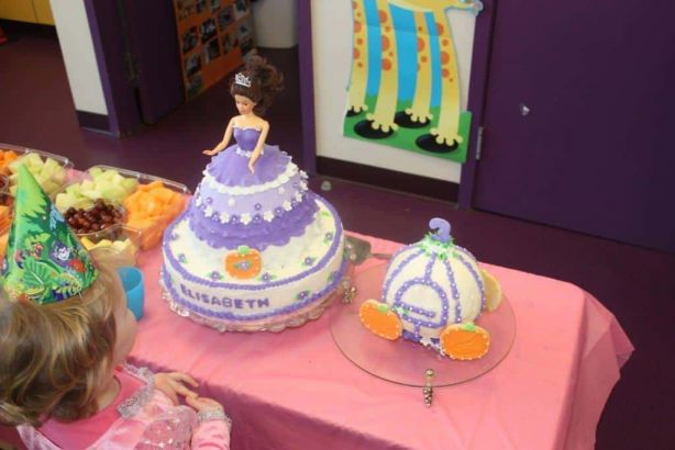 Princess birthday guest admiring masterpiece princess cake and carriage