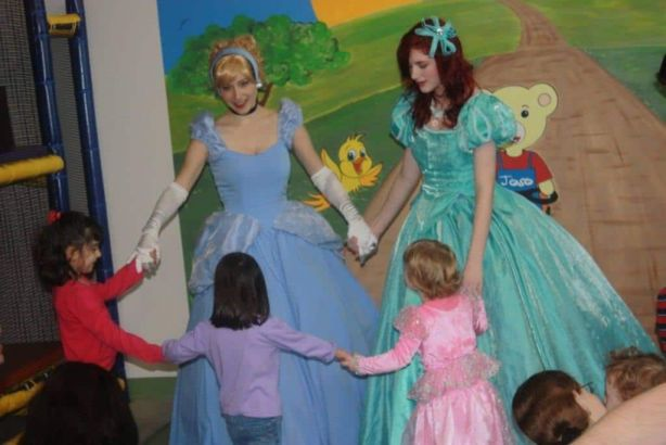 Princess Cinderella and Princess Little Mermaid dancing with little princesses
