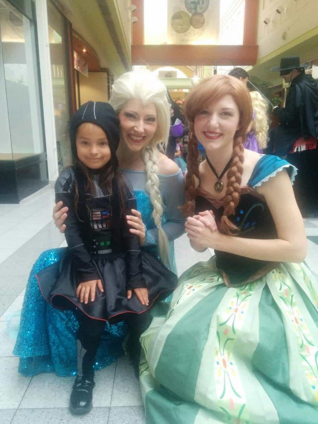 Girl sitting on Ice Queen's lap with Snow Princess at Calgary's Northland Mall Halloween event