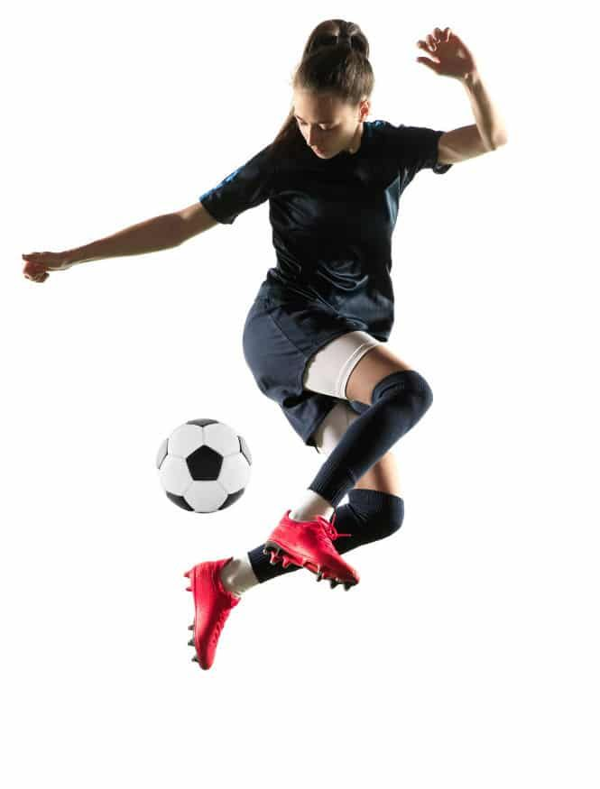 A young woman leaps in the air to kick a soccer ball