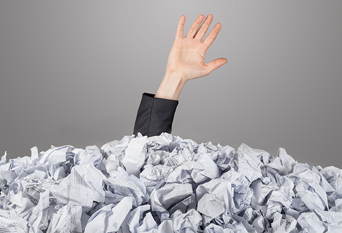 hand reaching out from pile of paper containing an overload of information