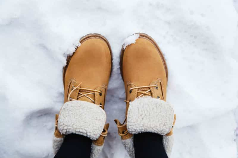 A person wearing a pair of boots in the snow