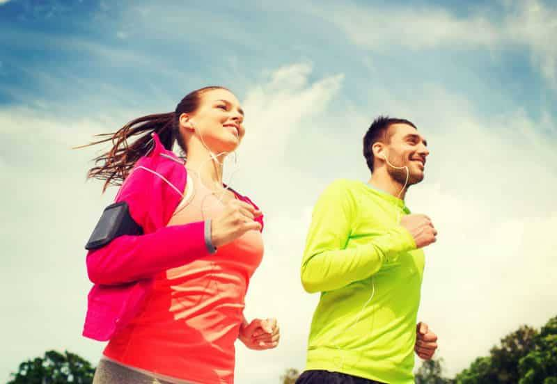 A man and a woman are running in bright clothes with earplugs in