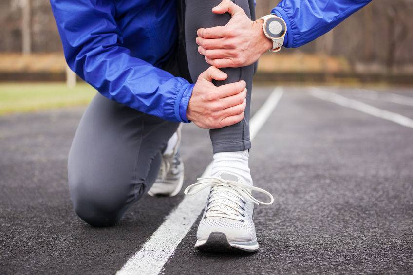 A man crouches down by the side of the road holding his left shin with both hands