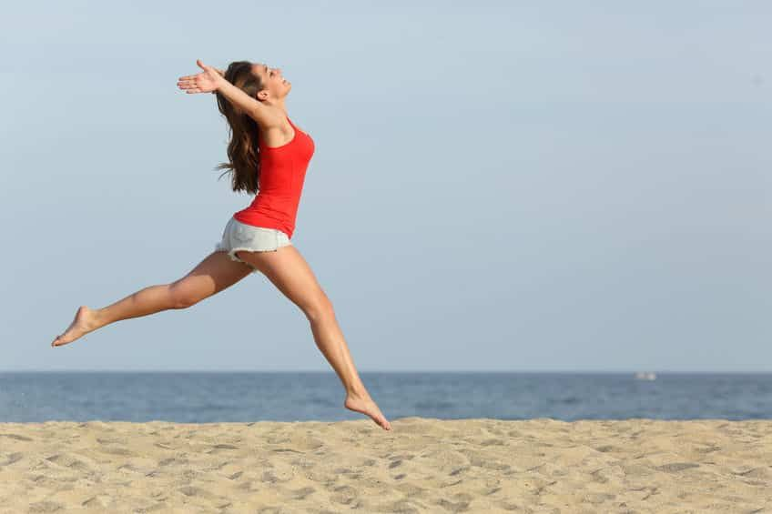 A lady leaping in joy on the beach