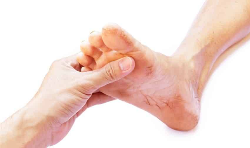 A hand holding a dirty foot