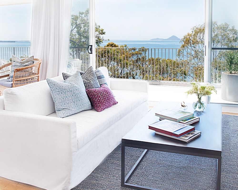 a living room with modern white sofa, image centers on view out window to the ocean and headlands